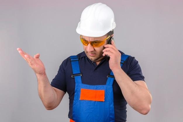 建設の制服と安全ヘルメットを身に着けている中年の怒っているビルダー男怒ってイライラして分離の白い壁に携帯電話で話しているヘルメット