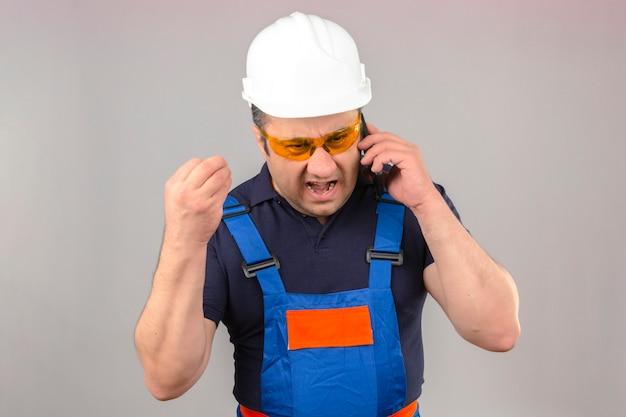 建設の制服と安全ヘルメットを身に着けている中年の怒っているビルダー男怒り狂った怒りで叫び、孤立した白い壁に上げられた手で叫んで携帯電話で話しています。