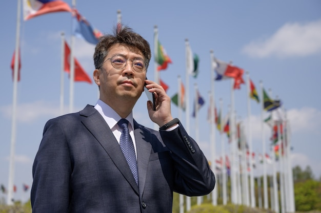 風になびくさまざまな国旗の下でスマートフォンを使用している中年のアジア人ビジネスマン。