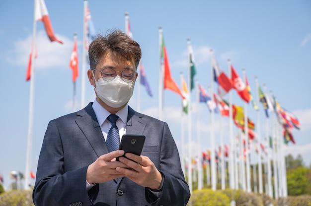 風になびくさまざまな国旗の下でマスクを着用し、スマートフォンを使用している中年のアジア人ビジネスマン。