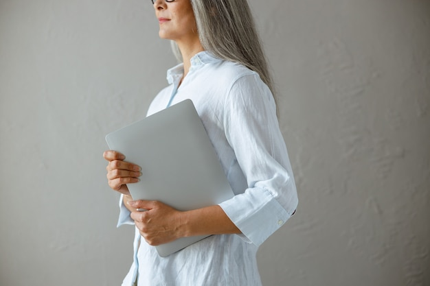 Middle aged asian businesswoman wearing white blouse holds modern laptop standing near grey stone wall in studio side view closeup