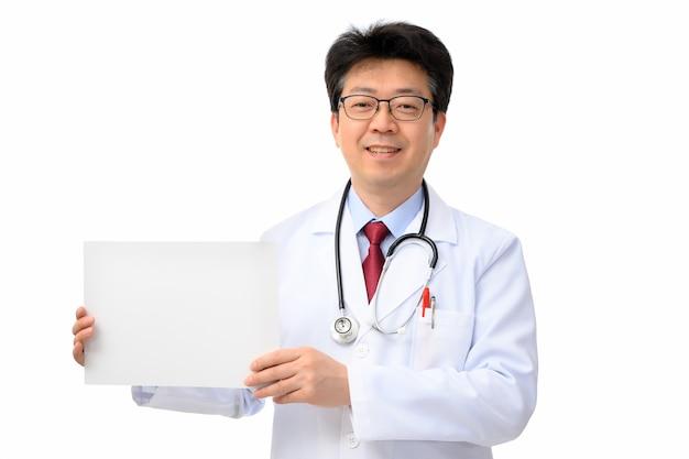 白い背景の上のメッセージボードを保持している中年のアジアの医者。