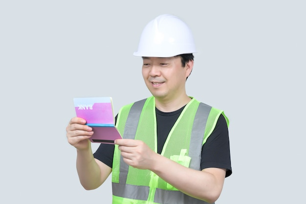 Middle-aged asian engineer holding a bank passbook