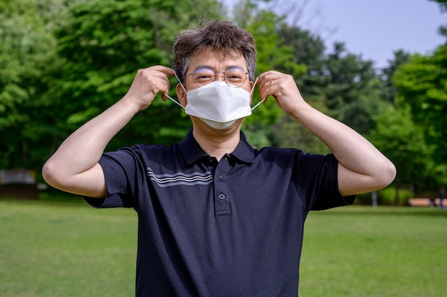 Азиатский мужчина средних лет в маске на лужайке.