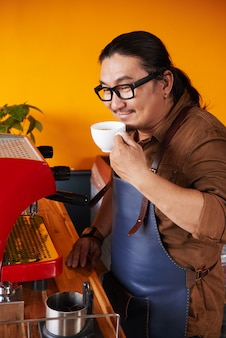 Middle-aged asian man in apron standing next to coffee machine and holding cup to nose
