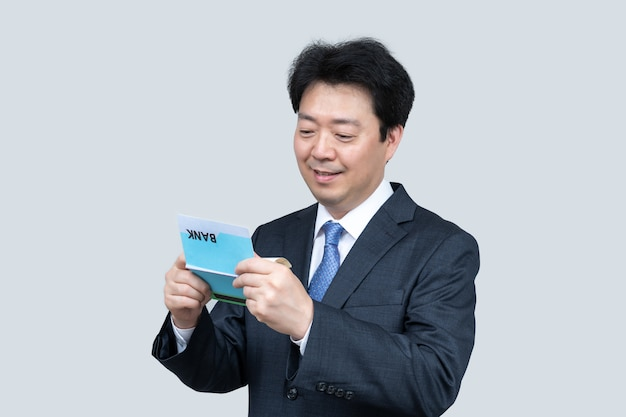 Азиатский мужчина средних лет держит банковскую книжку