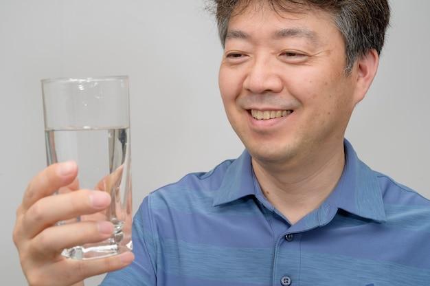 Азиатский мужчина средних лет, держащий стакан воды.