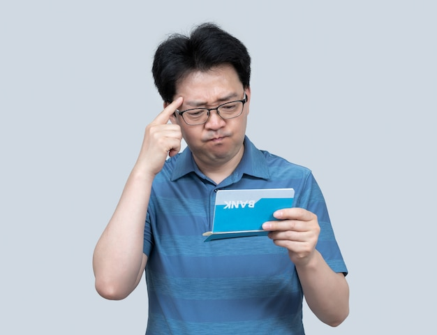 A middle-aged asian man holding a bank passbook in his hand