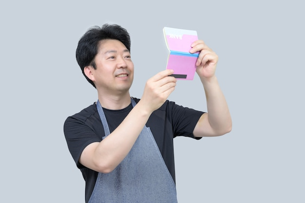 Middle-aged asian man holding a bank passbook