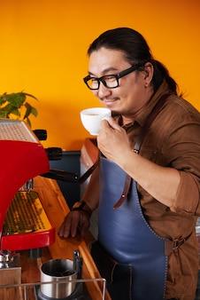 エプロンコーヒーマシンの隣に立って、鼻にカップを保持している中年のアジア人