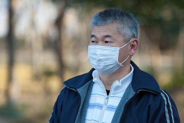 コロナウイルスからの保護のために白いサージカルマスクを身に着けている屋外の中年アジア人男性