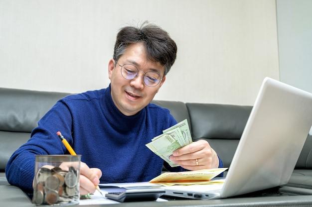 세금 환급을 준비하는 중년 아시아 남자.