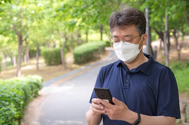 Азиатский мужчина средних лет идет в одиночестве по лесной тропинке в маске.