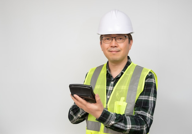 A middle-aged asian man wearing a white work cap and work suit holding a calculator in his hand.