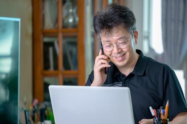 Азиатский мужчина средних лет, работающий дома. концепция удаленной работы.