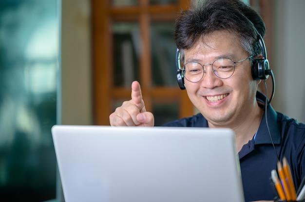 在宅勤務の中年アジア人男性。在宅勤務の概念。