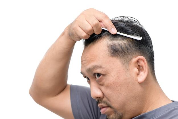 Азиатский мужчина средних лет беспокоится о выпадении волос или облысении и изолировании седых волос