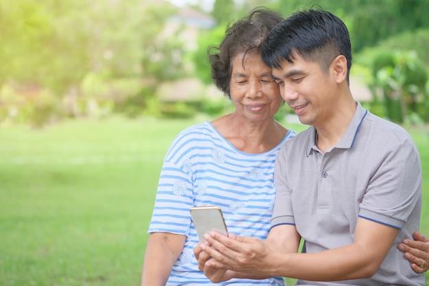 Азиатские мать и сын средних лет глядя на смартфон с улыбкой и быть счастливым в парке, это впечатляющее тепло