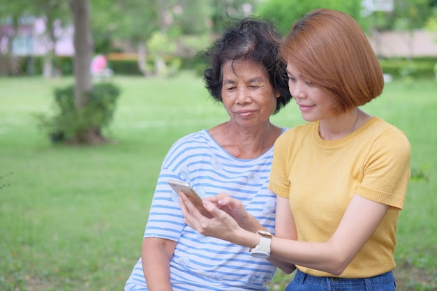 Middle-aged asian mother and daughter looking at a smartphone with a smile and being happy at the park is an impressive warmth