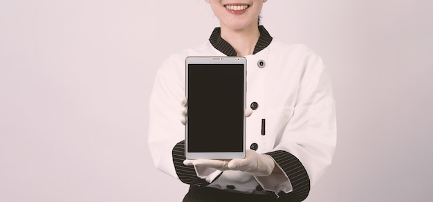 Middle aged of asian woman chef holding smartphone or digital tablet and received order from online