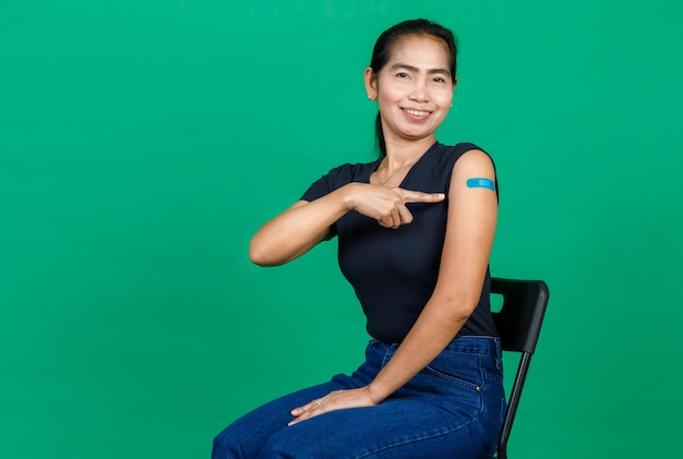 Middle aged asian woman smiling pointing at her arm with bandage patch showing she got vaccinated for covid 19 virus on green background. concept for covid 19 vaccination.