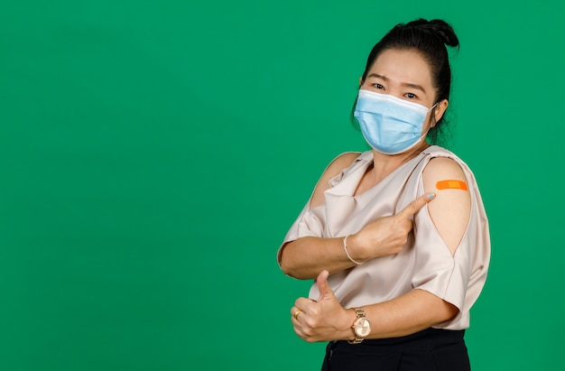 Middle aged asian woman wearing face mask and pointing at her arm with bandage patch showing she got vaccinated for covid 19 virus on green background. concept for covid 19 vaccination.