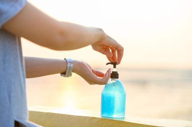 中年のアジアの女性はアルコールジェルで手を洗ってコロナウイルスを防ぎます