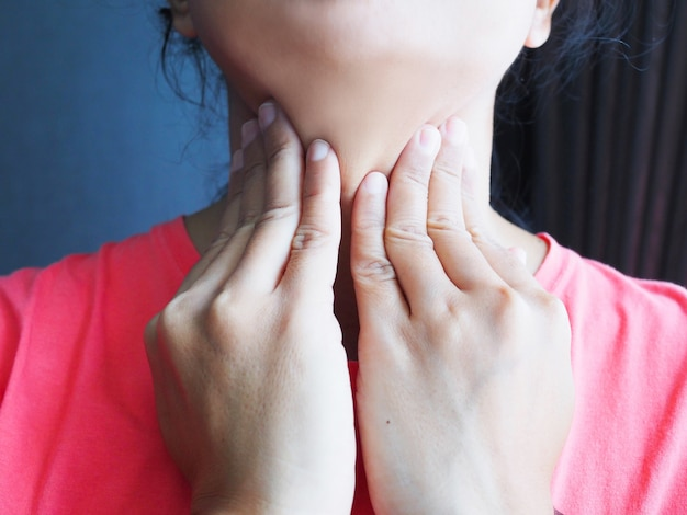 Middle-aged asians use hands to touching neck with symptom sore throat.