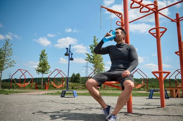 中年のアスリートであるヨーロッパ系白人のスポーツマンは、美しく暖かい晴れた日に屋外でトレーニングした後、ボトルから水を飲みます。ハンサムな男男マッチョは運動した後、彼の体を水分補給します
