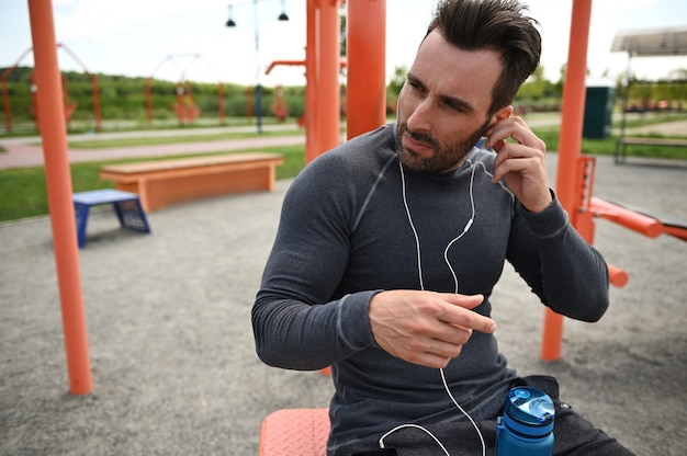 Middle-aged athlete listens to music on headphones, rests between sets during training on the background of a sports field