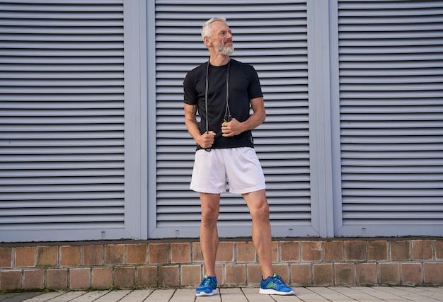 屋外に立っている縄跳びを保持しながら脇を見てスポーツウェアの中年アスリート男