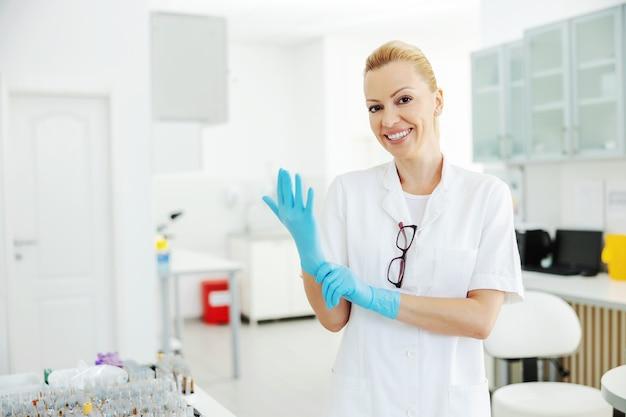 研究室に立って、無菌のゴム手袋を着用し、研究を行う準備をしている、無菌の白い制服を着た中年の魅力的な実験助手。