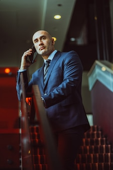 Лысый бизнесмен средних лет остановился на лестнице, держа смартфон с помощью мобильного телефона в