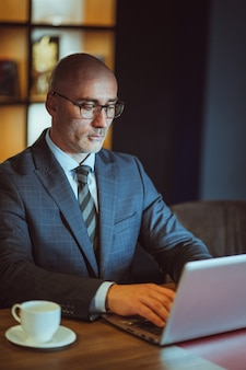 Middle aged bald businessman in suite working on laptop sitting in the modern office. handsome bold