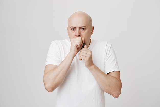 Middle-aged bald man coughing in fist