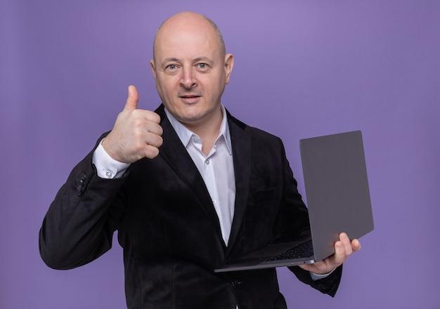 Лысый мужчина средних лет в костюме держит ноутбук, глядя вперед, улыбаясь, уверенно показывая большой палец вверх, стоя над фиолетовой стеной