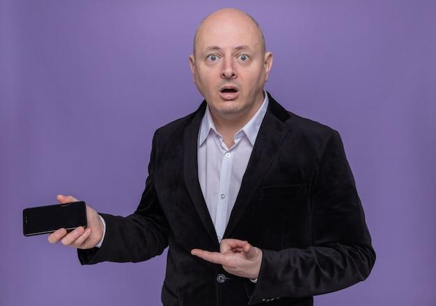 Лысый мужчина средних лет в костюме держит мобильный телефон, указывая на него указательным пальцем, смущенный, стоя у фиолетовой стены