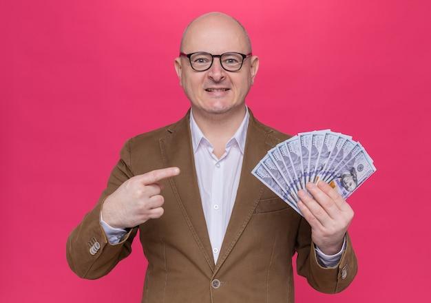 Лысый мужчина средних лет в костюме в очках с деньгами смотрит вперед, указывая указательным пальцем на деньги, счастливый и позитивный, стоя над розовой стеной
