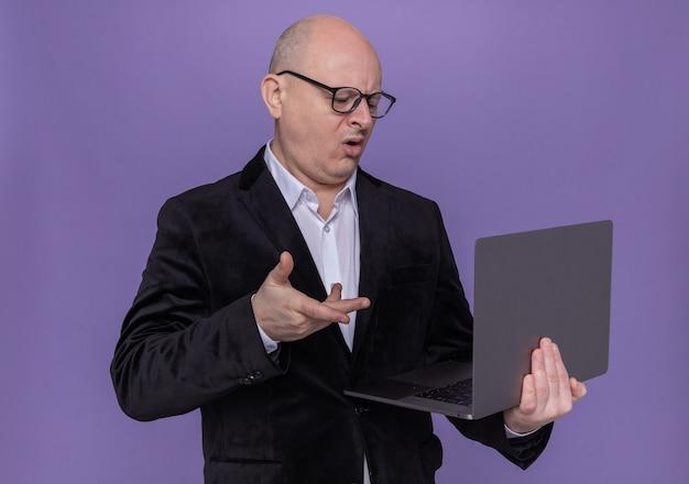 Лысый мужчина средних лет в костюме в очках держит ноутбук и смотрит на экран, смущенный и недовольный, стоя над фиолетовой стеной