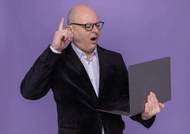 紫色の壁の上に立っている新しいアイデアを持っている人差し指を示して驚いたように見えるラップトップを保持している眼鏡をかけているスーツを着た中年のハゲ男