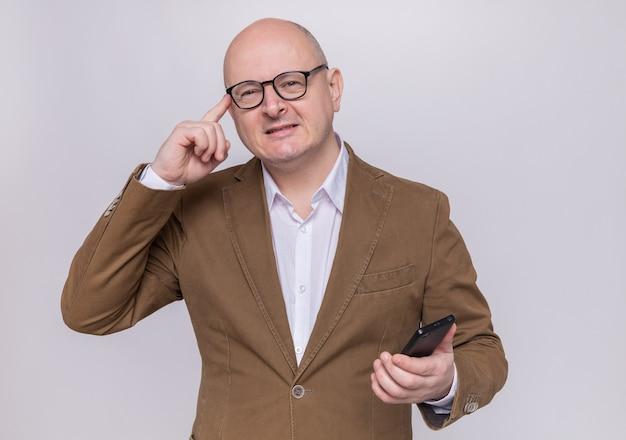 Лысый мужчина средних лет в костюме в очках держит мобильный телефон, касаясь пальцем его виска, концентрируясь на задаче, стоящей над белой стеной