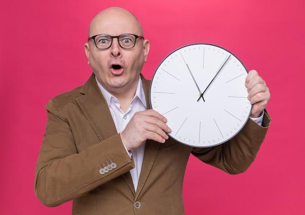 カメラを見て驚いた壁時計を保持している眼鏡をかけているスーツの中年ハゲ男