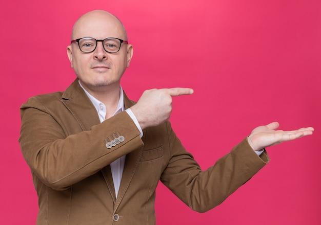 Лысый мужчина средних лет в костюме в очках смотрит вперед, улыбаясь, уверенно указывая указательными пальцами в сторону, стоя над розовой стеной