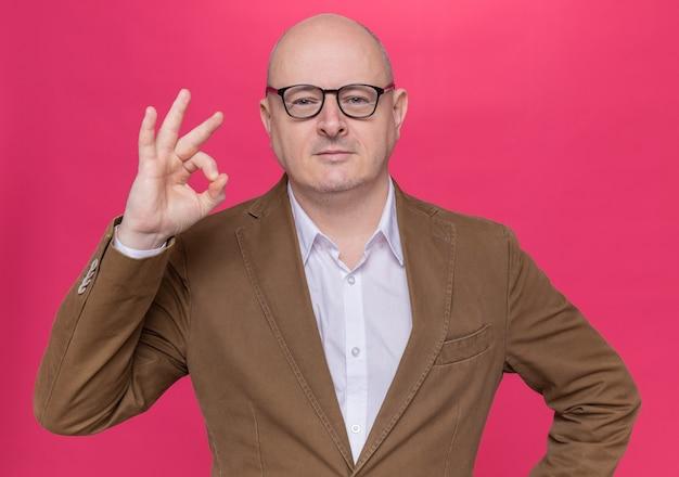 Лысый мужчина средних лет в костюме в очках, глядя вперед, улыбается, уверенно показывает знак ок, стоящий над розовой стеной