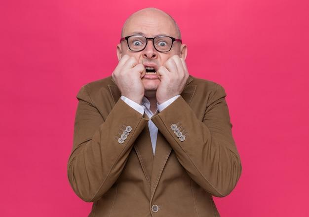 ピンクの壁の上に立っている正面のストレスと神経質な噛む爪を見て眼鏡をかけているスーツの中年のハゲ男