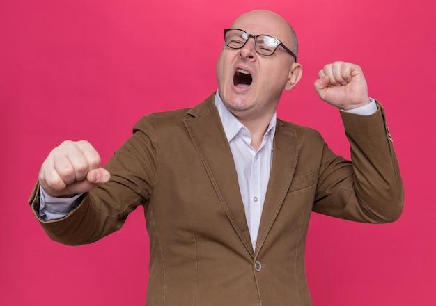 Лысый мужчина средних лет в костюме в очках кричит, когда его раздражают, сжимая кулаки