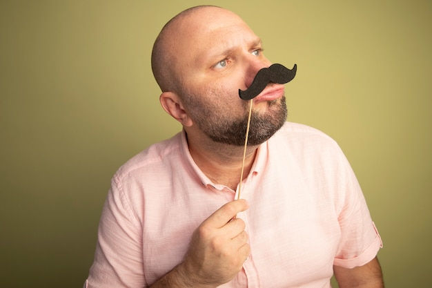 Middle-aged bald man looking at side wearing pink t-shirt holding fake mustache on stick isolated on olive green