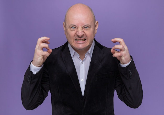 Uomo calvo di mezza età in vestito che si scatena alzando le braccia urlando con espressione aggressiva in piedi sopra il muro viola