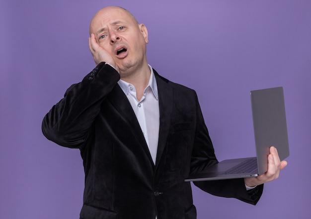 Uomo calvo di mezza età in vestito che tiene laptop guardando davanti confuso con la mano sulla sua testa per errore in piedi sopra il muro viola