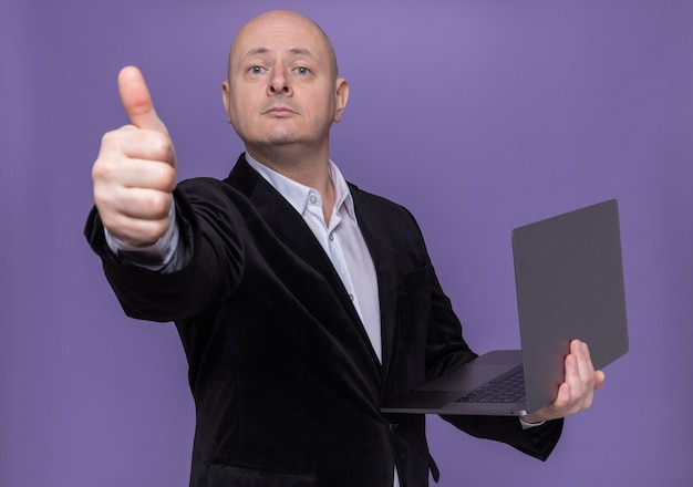 Middle-aged bald man in suit holding laptop looking at front with smile on smart face showing thumb up standing over purple wall